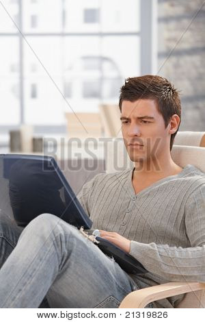 Handsome man concentrating on laptop computer screen, looking troubled, sitting in living room.?
