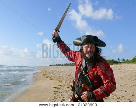 Pirate In Vintage Costume On The Beach Raises His Sword To Attack.