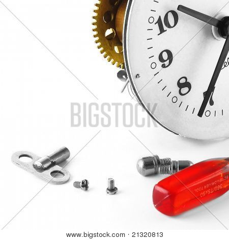 Broken clock with screws and red screwdriver