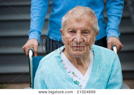 Senior lady in wheelchair with caretaker
