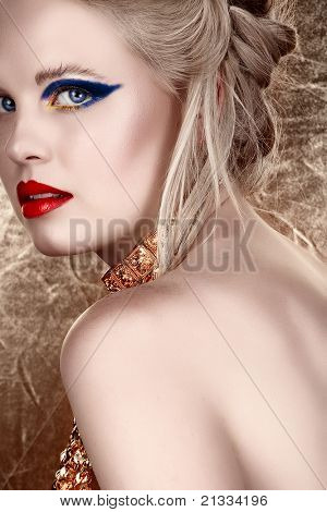 beautiful blond with hair in upstyle wearing dark fashion eyeshadow and red lips looking over shoulder on gold background in sepia fashion effect
