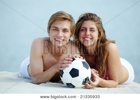 Photo of pretty girl and handsome guy with ball looking at camera on sandy beach