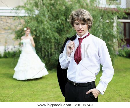 Portrait of a young bride in nature in a dark suit and red tie