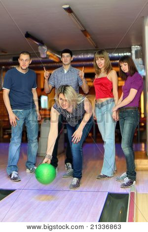 Girl prepares for throw  ball in bowling and friends hearten it, focus on girl in center