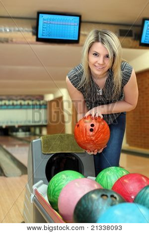 Girl takes two hands ball for playing bowling