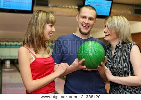 Two girls and man stand alongside and laugh merrily, focus on man