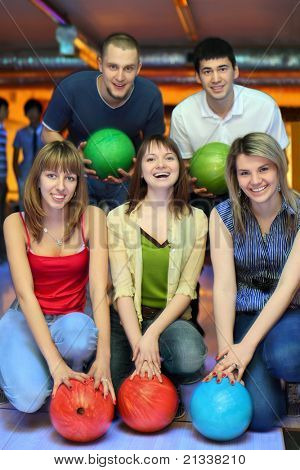 Three girlfriends squatting and behind stands two fellows  and everybody holds ball for bowling, focus on girls