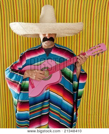 Mexican typical man with poncho and sombrero playing guitar