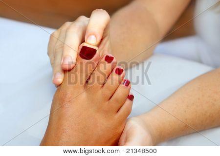 Unhas vermelhas de terapia de massagem de pés de mulher de reflexologia