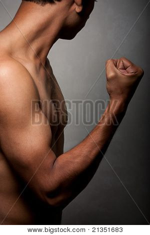 Portrait of young Indian angry man over dark