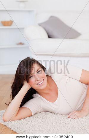 Charmante Brünette Frau, die beim liegen auf dem Teppich im Wohnzimmer