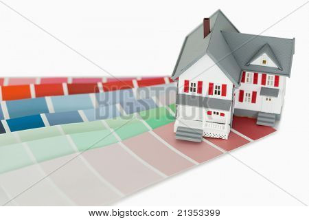 A miniature house and a color chart against a white background