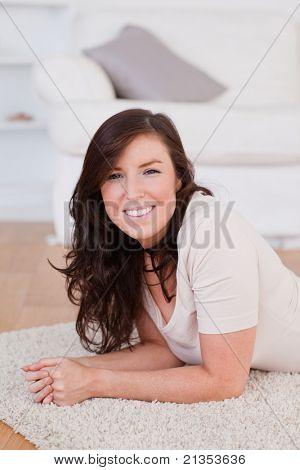 Gut aussehende Brünette Frau posiert beim liegen auf dem Teppich im Wohnzimmer
