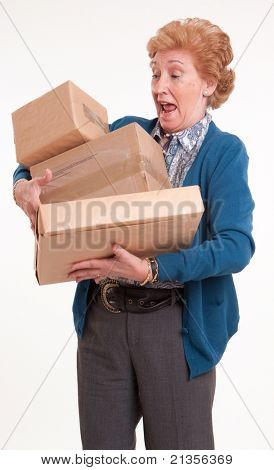 Senior woman holding a lot of parcels with alarm