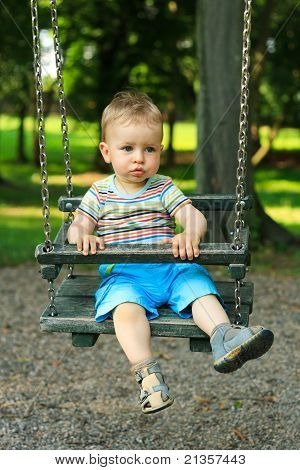 A Handsome Little Boy Swinging At The Playground In The Park