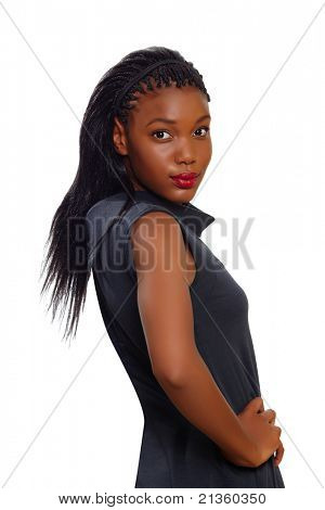 African American business woman stands confident with arms on her side and looking over her shoulder on white background