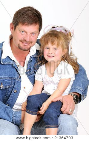 young father dressed in jeans and toddler girl dressed in white smiling lovingly sitting on lap