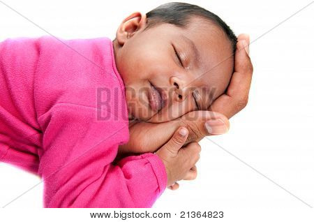 sweet newborn baby girl in pink peaceful and asleep in farther hands