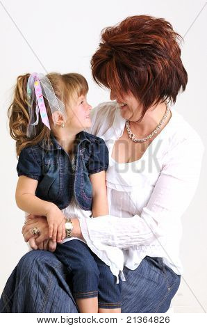 young daughter kissing mother on the cheek and smiling