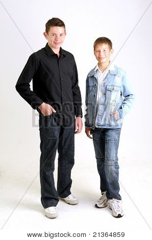 young attractive boys wearing blue jean jacket black shirt respectively standing and smiling
