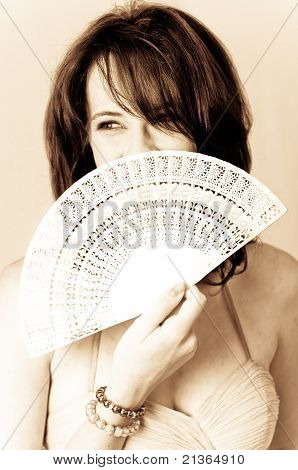 Sepia image of beautiful young brunette sexy model holding a white with Chinese hand fan in face