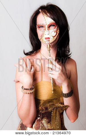 Beautiful young brunette sexy model with colorful red and gold venetian carnival face mask