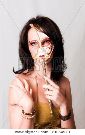 Beautiful young brunette haired blue eyed sexy model with colorful venetian face mask