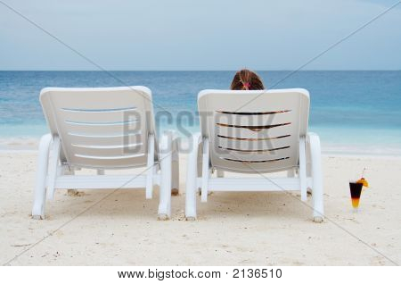 Two Chaise-Longue On The Beach. One Of Them Is Empty.