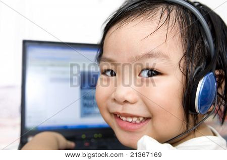 Young preschool girl, listening to music or a video on a laptop computer.