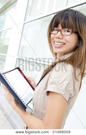 Great smiling outdoor young executive with documents