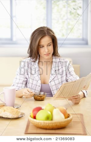 Portrait of young woman reading papers at breakfast table, having cereal.?