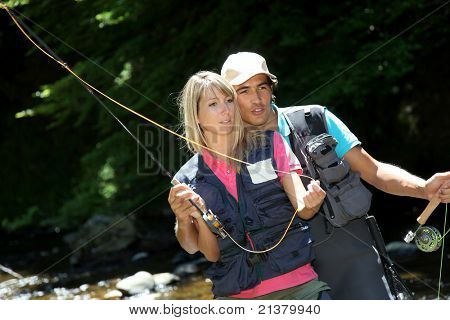 Couple fly fishing in river during summer vacation