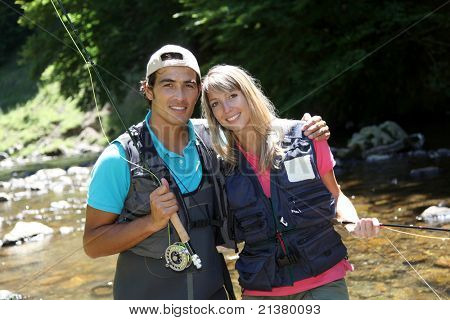 Portrait of couple fly fishing in river