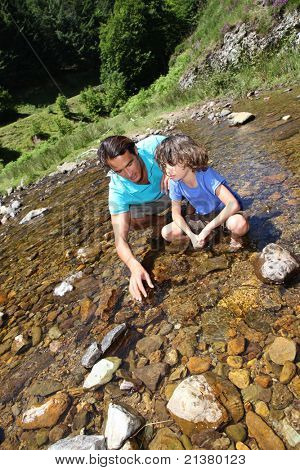 Father and son playing with peebles in river