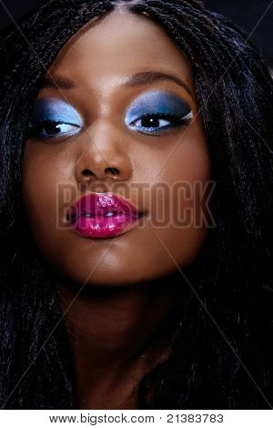 beautiful African woman portrait with bright pink lips and dark artistic eyeshadow with long extensions hairstyle in low key light