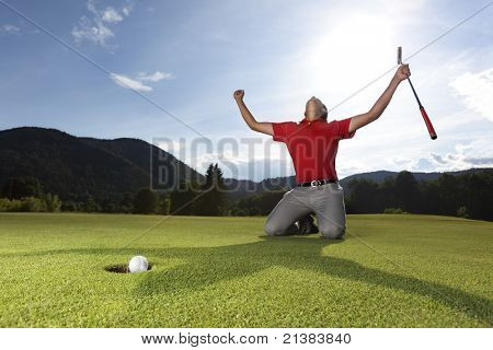 Professional young male golf player on knees and arms raised with putter in hand on golf green being overjoyed as golf ball drops into cup.