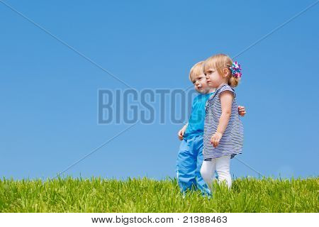 Two kids embracing, gazing afar