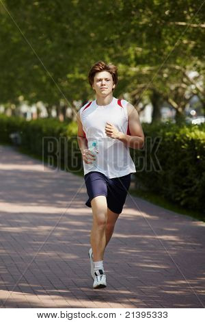 Portrait of active young man jogging in park