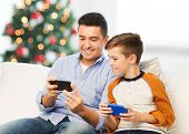 technology, family and people concept - happy father and son with smartphones texting message or pla poster