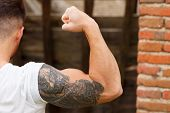 Strong guy with a tattoo on his arm in al old house poster