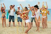 foto of wedding couple  - Beach wedding of happy newlywed couple have fun doing the limbo - JPG