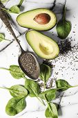 Fresh healthy ingredients for a breakfast on a marble table. Healthy life concept with avocado,chia  poster