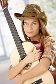 Attractive guitar player girl hugging her guitar, smiling, wearing western hat.?