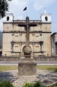 stock photo of escuela  - Cross on the square and church Escuela de Cristo in Antigua - JPG
