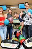 Two girls and two youths stand near tenpin bowling with balls for playing bowling and smile, focus o