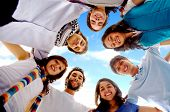 picture of blue sky  - group of happy friends smiling with heads together outdoors with a blue sky in the background - JPG