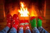 Family In Christmas Socks Near Fireplace poster