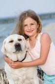 Постер, плакат: Лучшие друзья маленькая девочка с собакой на пляже