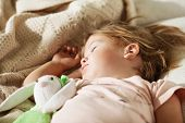 Sleeping Little Girl. Carefree Sleep Little Baby With A Soft Toy On The Bed. poster