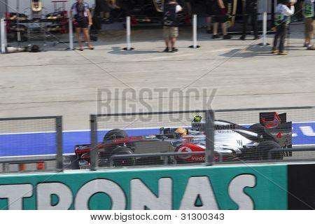 Lewis Hamilton drives through the pit lane